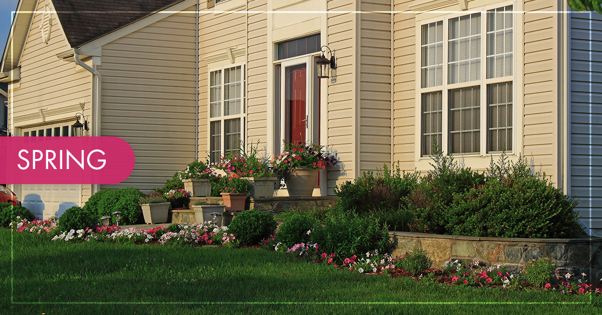 The exterior of a home with fresh blooming bushes and flowers and a green lawn.