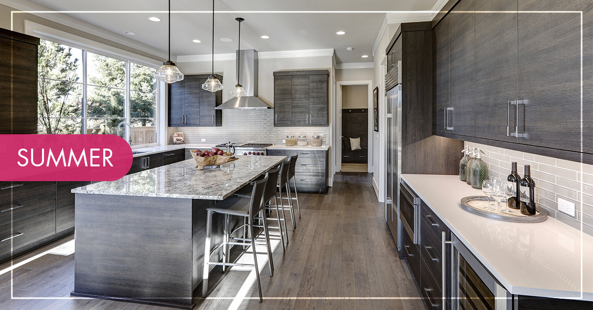 A bright kitchen with dark grey wood cabinets and marble white and grey countertops.