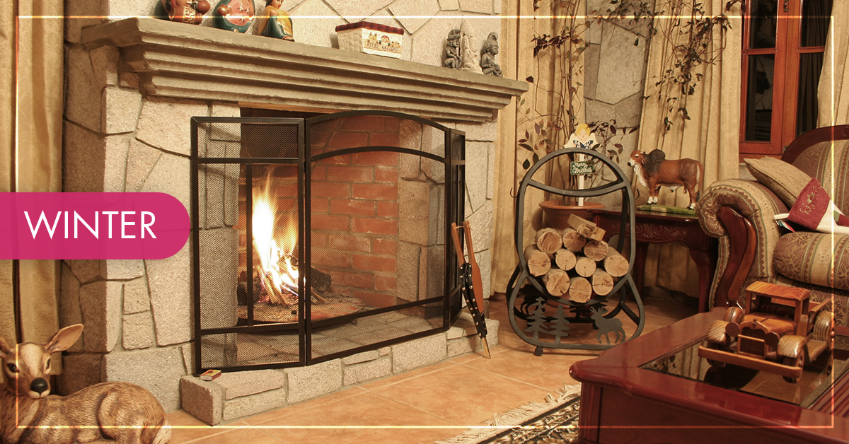 A cosy living room with a burning fire in a stone fireplace.
