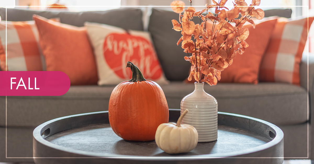 A living room with a grey couch decorated with orange fall pillows and a coffee table with pumpkins and fall leaves in a vase.